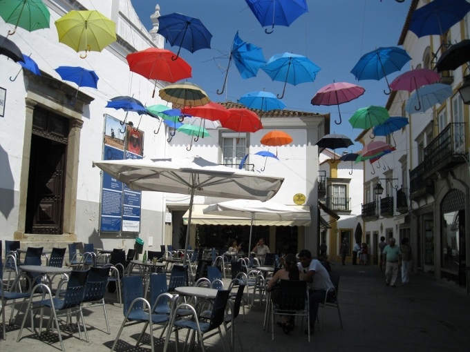 Rua de Évora sombreada por chapéus de chuva